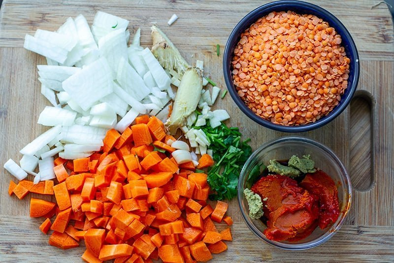 Instant Pot red lentil soup ingredients: onions, ginger, garlic, carrots, lentils, curry paste, coriander