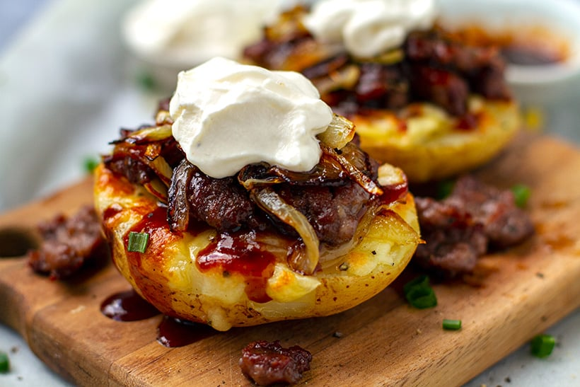 Stuffed potatoes with sausage, onions, BBQ sauce and sour cream